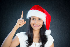 AHA. Closeup portrait of happy christmas woman, with red hat, pointing with index finger, aha i have an idea, positive human facial expression, isolated on grey Royalty Free Stock Photo