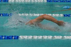Ahead of the competitor. Freestyle swimmer powering ahead in 100m race Royalty Free Stock Photos