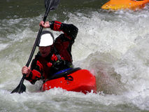 Ahead by a Length. Kayaker racing down a mountain river Royalty Free Stock Images