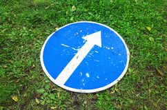 Ahead only, round blue road sign on grass. Ahead only, round blue road sign with white directional arrow lays on green grass royalty free stock photos