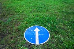 Ahead only, round blue road sign, concept. Ahead only, round blue road sign with white arrow lays on green grass stock images