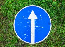 Ahead only, blue road sign lays on grass. Ahead only, round blue road sign with white directional arrow lays on green grass, top view royalty free stock photography
