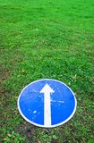 Ahead only, blue road sign lays on lawn. Ahead only, round blue road sign with white directional arrow lays on green grass, vertical photo stock image