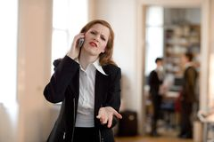 Ahh come on!!!. Businesswoman is talking on the phone and her colleagues are standing in the back Stock Image