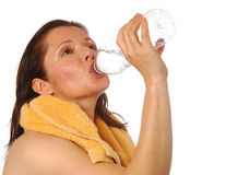 Ahh, refreshing!. Pretty woman taking a swig of bottled water after a workout Royalty Free Stock Photo