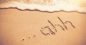 Ahh written on sand at beach with waves Royalty Free Stock Photography