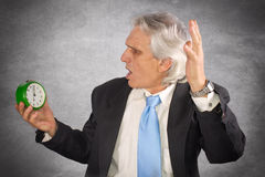 Ahhh. Businessman holding a clock in panic and late for work Stock Photography