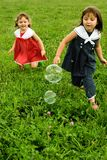 Ahhh to Be Young... Chasing Bubbles Royalty Free Stock Photos
