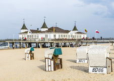 Ahlbeck Pier. AHLBECK, GERMANY - APRIL 20, 2014: Ahlbeck pier, a landmark of Usedom Island. In the foreground there are several beach chairs, which are typical Royalty Free Stock Image