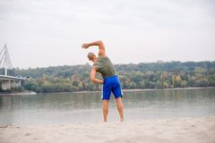 Ahlete work out on beach. Barefoot and wearing sport`s shorts and sleeveless Royalty Free Stock Images