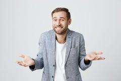 Ahnungsloser verwirrter attraktiver Mann mit Bart, breit lächelnd und haben das zuckende Schulterausdrücken des Zögerns stockbild