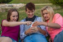 ¡Ahora mi vuelta! Tres amigos que luchan para un teléfono móvil Foto de archivo libre de regalías