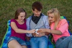 ¡Ahora mi vuelta! Tres amigos que luchan para un teléfono móvil Imagenes de archivo