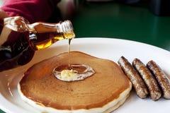 Ahornholz-Sirup auf Pfannkuchen mit Wurst Lizenzfreies Stockfoto