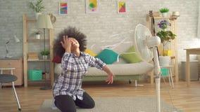 Ahorran a la mujer africana con un peinado afro delante de la fan de calor almacen de metraje de vídeo