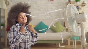 Ahorran a la mujer africana dejada perplejo con un peinado afro delante de la fan del calor MES lento almacen de metraje de vídeo