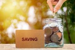 Ahorrando e invierta el concepto del dinero Mano conceptual que pone monedas i imagen de archivo libre de regalías