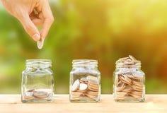 Ahorrando e invierta el concepto del dinero Mano conceptual que pone monedas i imágenes de archivo libres de regalías
