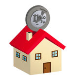 Ahorrar casa. Coins inserted in house-shaped piggy bank Royalty Free Stock Photos