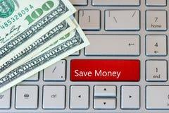 Ahorre el botón rojo del dinero en el teclado del ordenador portátil con los billetes de banco del dólar Visión superior fotografía de archivo