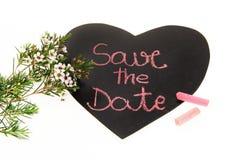 Ahorre el texto de la fecha en la pizarra en forma de corazón con las flores en la floración aislada en el fondo blanco imagen de archivo libre de regalías