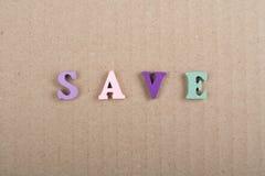 AHORRE la palabra en el fondo de papel compuesto de letras de madera del ABC del bloque colorido del alfabeto, copie el espacio p Fotografía de archivo libre de regalías