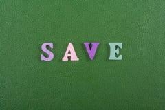 AHORRE la palabra en el fondo verde compuesto de letras de madera del ABC del bloque colorido del alfabeto, copie el espacio para Fotografía de archivo libre de regalías