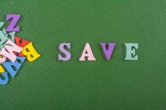 AHORRE la palabra en el fondo verde compuesto de letras de madera del ABC del bloque colorido del alfabeto, copie el espacio para Fotos de archivo libres de regalías