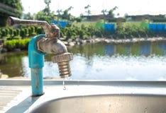 Ahorre la reserva del agua el concepto del mundo, descenso del agua del grifo defectuoso en la esquina por el río con el espacio  fotos de archivo libres de regalías