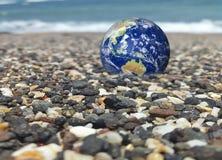 Ahorre la tierra, tierra generada por ordenador como el planeta en una playa Onda que machaca en el fondo Concepto conveniente pa imagen de archivo
