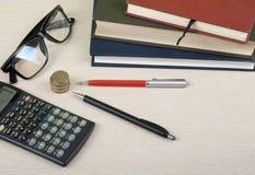 Ahorros caseros, concepto del presupuesto Libreta, calculadora, lápiz, lentes y monedas en la tabla de la oficina Imagen de archivo libre de regalías