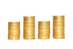 Ahorros, columnas cada vez mayores de las monedas de oro aisladas en la parte posterior del blanco Foto de archivo libre de regalías