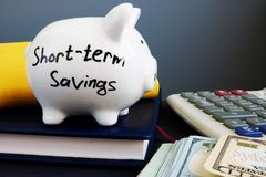 Ahorros a corto plazo Hucha, calculadora y dinero foto de archivo