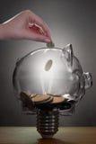 Ahorros de la bombilla de Piggybank Foto de archivo libre de regalías