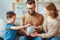 Ahorros de la familia, planeamiento del presupuesto, dinero suelto de los ni?os Familia con la bater?a guarra imágenes de archivo libres de regalías