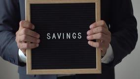 Ahorros de la palabra de letras en tablero del texto en el hombre de negocios anónimo Hands almacen de video