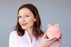 Ahorros del dinero ninguna mujer de la tensión que sostiene la hucha del moneybox imagen de archivo