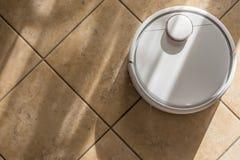 Ahorros del tiempo en el hogar con cuidado del piso con un robot elegante del vacío foto de archivo