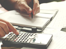 Ahorros, finanzas, economía y concepto casero - cercanos para arriba de hombre con la calculadora que cuenta haciendo notas en ca imagen de archivo libre de regalías