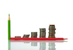 Ahorros, monedas cada vez mayores de las columnas y lápiz en b blanco Fotografía de archivo