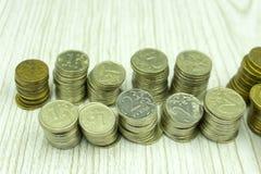 Ahorros que aumentan columnas de las monedas de oro sobre el fondo blanco foto de archivo