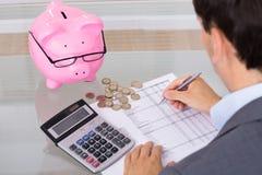 Ahorros y costes calculadores del hombre Imagen de archivo libre de regalías