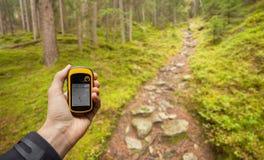 AHRNTAL, ИТАЛИЯ - 26-ОЕ СЕНТЯБРЯ 2014: Trekker находит правое положение в лесе через gps в пасмурном осеннем дне Стоковая Фотография RF