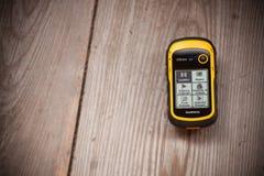 Ahrntal Italien - Oktober 11, 2014: Den GPS Garmin mottagaren är recordindpositioneringjournalen över en träbakgrund Royaltyfria Bilder