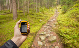Ahrntal, Italy - September 26, 2014: A trekker is finding the right position in the forest via gps in a cloudy autumnal day Royalty Free Stock Photography