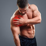 Ahtletic muscle man Shoulder pain. Bodybuilder with shoulder pain over gray background. Concept with highlighted glowing red spot Stock Photography