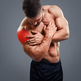Ahtletic muscle man Shoulder pain. Bodybuilder with shoulder pain over gray background. Concept with highlighted glowing red spot Royalty Free Stock Image