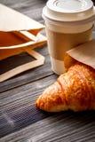 Ahueque el café y el cruasán en bolsa de papel en fondo de madera Fotografía de archivo libre de regalías
