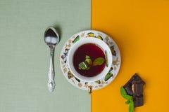 Ahueque el té con la menta en la tabla de lino y los pedazos de la barra de chocolate fi Imagen de archivo