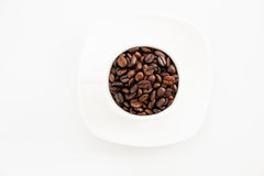 Ahueque los granos de café llenos en un fondo blanco Fotos de archivo libres de regalías